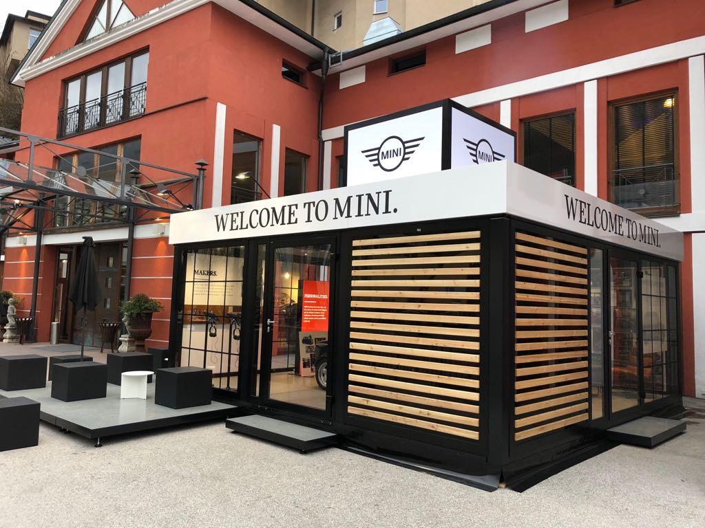 MINI am Wolfgangsee - Modell LongTail / mit umlaufender Attika, Terrasse, Verglasung und mehreren Türen, Boden in Beton-Optik und Innenausbau. Kunde: Neonred